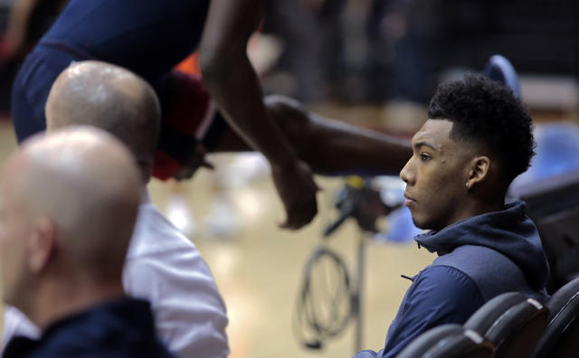 "Arizona guard <a class=""link rapid-noclick-resp"" href=""/ncaab/players/131287/"" data-ylk=""slk:Allonzo Trier"">Allonzo Trier</a>, right, sits courtside as teammates warm up before facing Oregon State last Thursday (AP)"