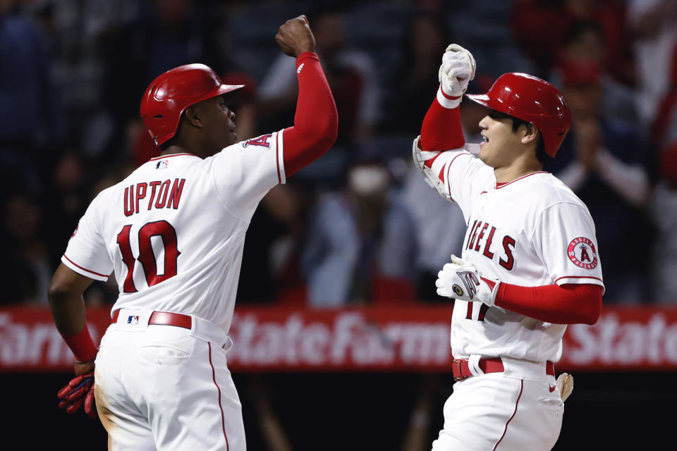 Los Angeles Angels' Shohei Ohtani, right, celebrates his two-run home run with Justin Upton during the fifth inning against the Detroit Tigers in a baseball game in Anaheim, Calif., Friday, June 18, 2021. (AP Photo/Alex Gallardo)