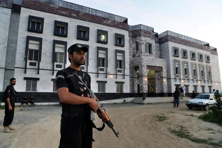 Pakistani policemen stand guard outside the hostel at Abdul Wali Khan university where students beat to death a classmate in Mardan on April 13, 2017