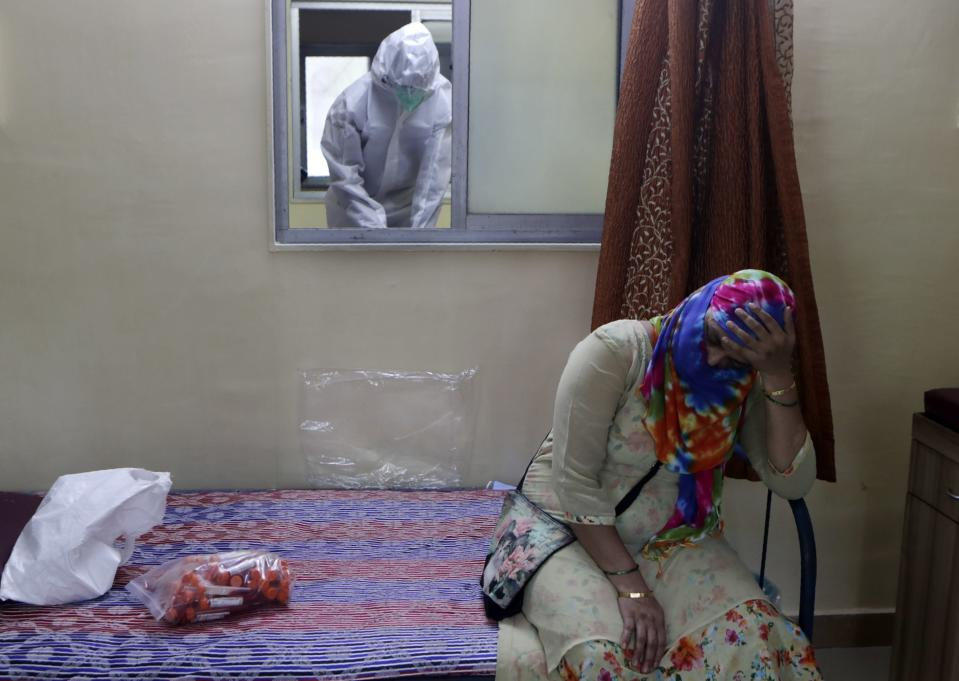 A woman waits to give a nasal swab sample to test for COVID-19 at a medical camp in Mumbai, India, Saturday, Aug. 8, 2020. As India hit another grim milestone in the coronavirus pandemic on Friday, crossing 2 million cases and more than 41,000 deaths, community health volunteers went on strike complaining they were ill-equipped to respond to the wave of infection in rural areas. (AP Photo/Rajanish Kakade)