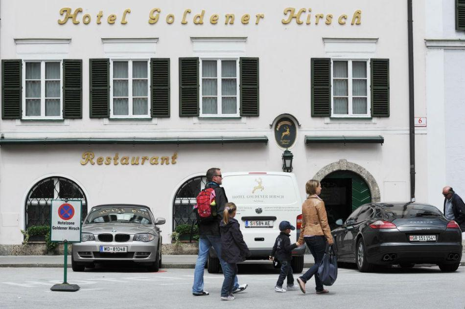 Tourists pass the front of the well-known luxury hotel Goldener Hirsch in Salzburg, Austria.