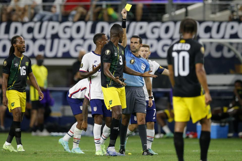 Jamaica forward Cory Burke (9) is issued a yellow card by referee Cesar Ramos, right center, as Daniel Johnson (16) and Bobby Reid (10) look on in the first half of a CONCACAF Gold Cup quarterfinals soccer match, Sunday, July 25, 2021, in Arlington, Texas. Burke received the card for knocking down United States midfielder Gianluca Busio during play. (AP Photo/Brandon Wade)