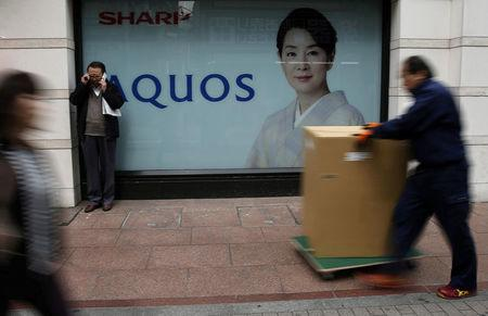 FILE PHOTO: People walk past an advertisement for Sharp Corp's Aquos television outside an electronics retail store in Tokyo