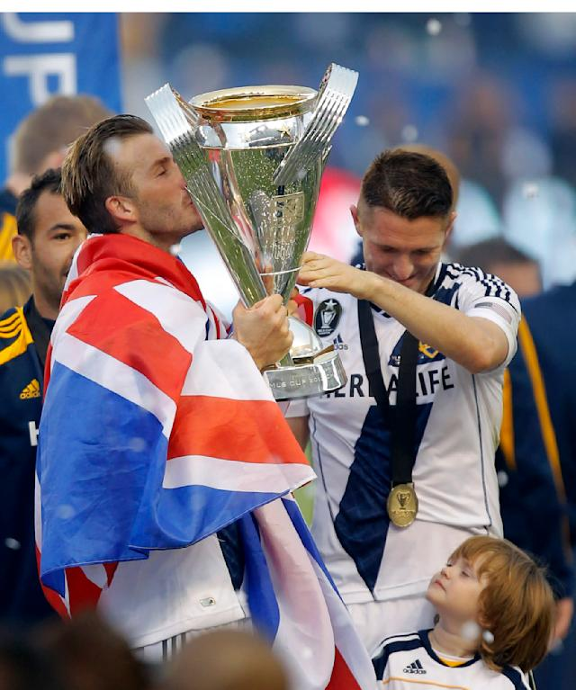 Los Angeles Galaxy's David Beckham, left, of England, kisses the trophy as he celebrates with Robbie Keane, or Ireland, after their 3-1 win in the MLS Cup championship soccer match against the Houston Dynamo in Carson, Calif., Saturday, Dec. 1, 2012. (AP Photo/Jae C. Hong)