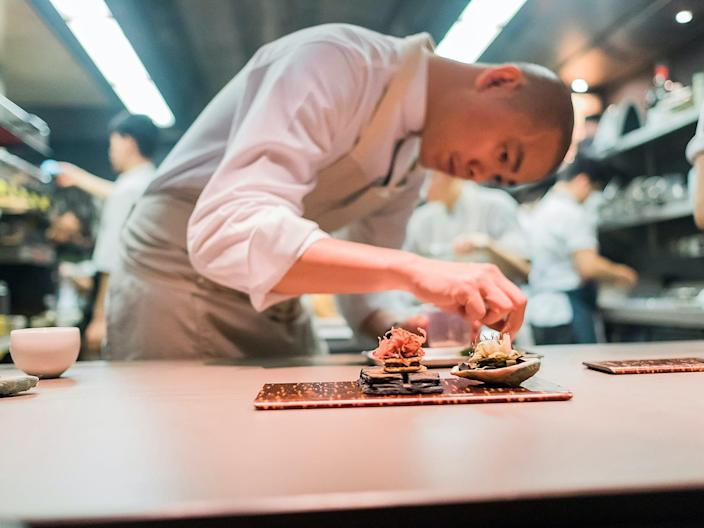 Chef Andre Chiang bending over a dish in his kitchen in Singapore to garnish a dish.