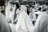 Seamstresses work on a dress at Christian Dior's Haute Couture fashion house workshop in Paris on January 20, 2021. With no catwalk fashion shows on offer, the artistic ambitions of fashion designers have gone virtual