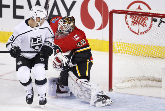 Los Angeles Kings' Dustin Brown, left, screens Calgary Flames goalie Cam Talbot as a shot by Anze Kopitar goes in for a goal during the first period of an NHL hockey game Saturday, Dec. 7, 2019, in Calgary, Alberta. (Larry MacDougal/The Canadian Press via AP)