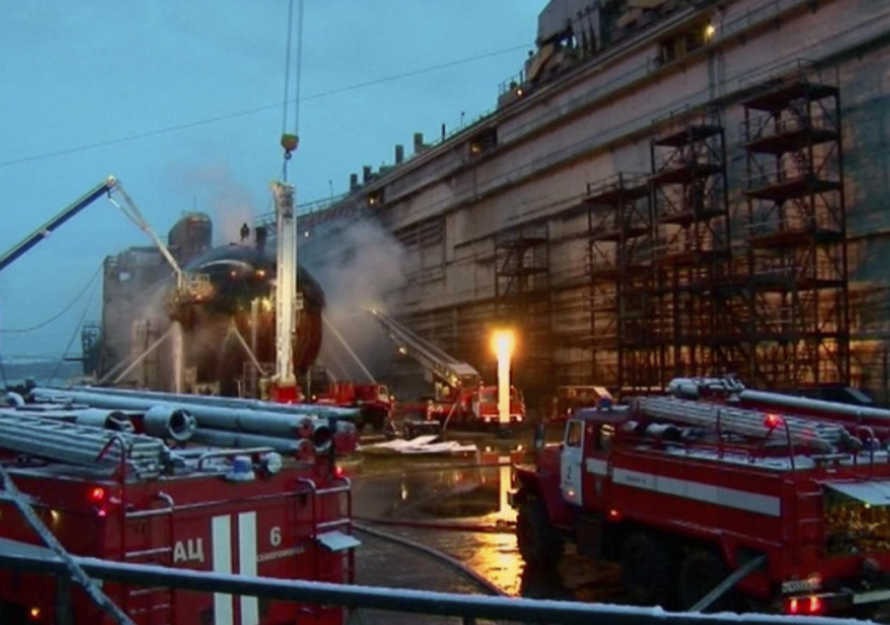 In this video image from Ru-RTR Russian state television channel, firefighters spray water on the Yekaterinburg nuclear submarine, left, in a dock at the Roslyakovo shipyard in the Murmansk region, Russia, Friday, Dec. 30, 2011. A fire that erupted while the Yekaterinburg was in drydock for repairs at the town of Roslyakovo near Murmansk has left seven crewmembers injured after they inhaled poisonous fumes from the blaze. (AP Photo/Ru-RTR Russian state channel/ Via APTN) TV OUT