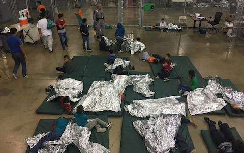 A view of inside a Texas detention facility shows children sleeping under foil sheets - Credit: Courtesy CBP/Handout via REUTERS