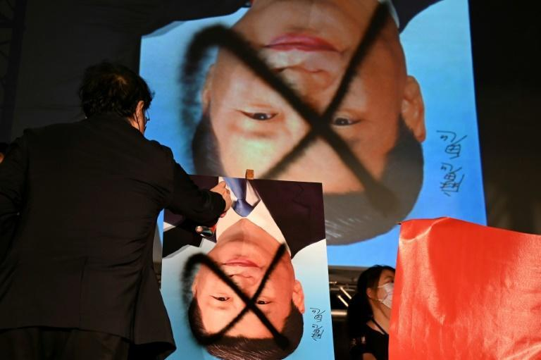 A demonstrator spray paints over a portrait of Chinese leader Xi Jinping during an anti-China rally outside the parliament in Taipei (AFP/Sam Yeh)