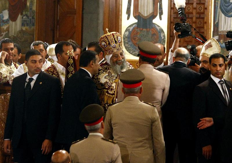 In this late Saturday, April 19, 2014 photo, Coptic Pope Tawadros II, center, greets a delegation from the Egyptian army at St. Mark's Cathedral during Easter Eve service, in Cairo, Egypt. Egypt's former military chief, retired Field Marshal Abdel-Fattah el-Sissi, and presumed presidential front-runner visited the Coptic pope earlier on Saturday ahead of Orthodox Easter, making his first public appearance since he formally made his bid for the presidency. (AP Photo/Ahmed Abdel Fattah, El Shorouk) EGYPT OUT