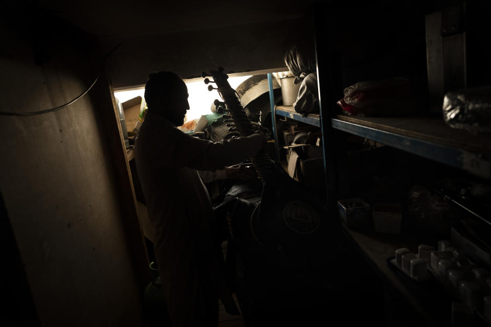 An Afghan man holds a sitar in a storage room in Kabul, Afghanistan, Tuesday, Sept. 21, 2021. About a month after the Taliban seized power in Afghanistan, the music is starting to go quiet. The last time that the militant group ruled the country, in the late 1990s, it outright banned music. (AP Photo/Bernat Armangue)