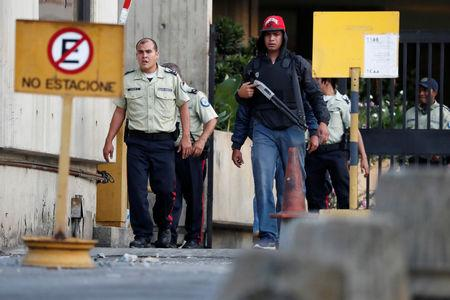 Security forces are seen after looting during an ongoing blackout in Caracas