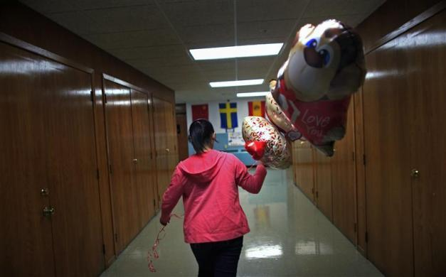 Jutarat Sawatpoon, a foreign exchange student from Thailand, walks through the halls to deliver balloons for the students at Grant-Deuel School, in Revillo, South Dakota February 13, 2012.