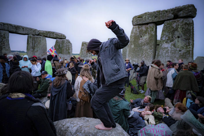 People inside the stone circle during Summer Solstice at Stonehenge, where some people jumped over the fence to enter the stone-circle to watch the sun rise at dawn of the longest day of the year in the UK, in Amesbury, England, Monday June 21, 2021. The prehistoric monument of ancient stones have been officially closed for the celebrations due to the coronavirus lockdown, but groups of people ignored the lockdown to mark the Solstice, watched by low key security. (Ben Birchall/PA via AP)