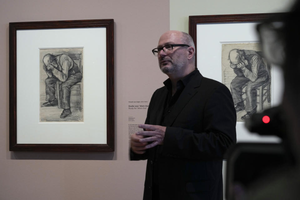 """Senior researcher Teio Meedendorp gestures during the presentation of Study for """"Worn Out"""", left, a drawing by Dutch master Vincent van Gogh, dated Nov. 1882, on public display for the first time at the Van Gogh Museum in Amsterdam, Netherlands, Thursday, Sept. 16, 2021. (AP Photo/Peter Dejong)"""