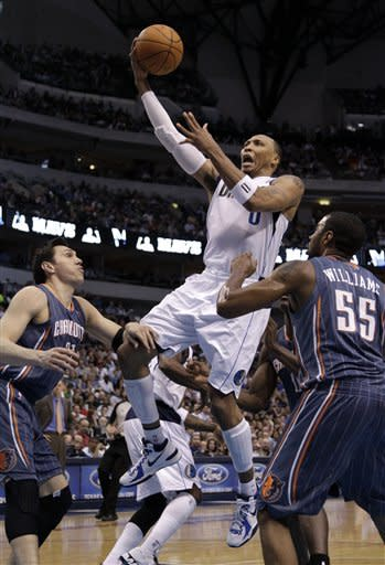 Dallas Mavericks small forward Shawn Marion (0) goes up for a shot over Charlotte Bobcats' Eduardo Najera, left, of Mexico, and Reggie Williams (55) in the first half of an NBA basketball game on Thursday, March 15, 2012, in Dallas. (AP Photo/Tony Gutierrez)