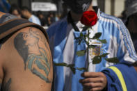 A mourner, sporting a tattoo of Diego Maradona on his forearm, waits in line to pay his final respects to the Argentine soccer great who died from a heart attack, in Buenos Aires, Argentina, Thursday, Nov. 26, 2020. Maradona's wooden casket was in the main lobby of the presidential office, covered in an Argentine flag and a No. 10 national team jersey. (AP Photo/Rodrigo Abd)