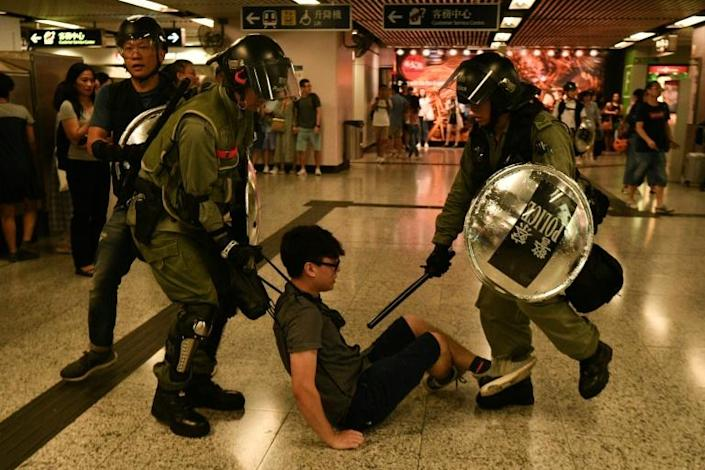 A suspected protester is detained by police inside Hong Kong's Causeway Bay MTR metro underground station, where officers fired tear gas outside (AFP Photo/Anthony WALLACE)