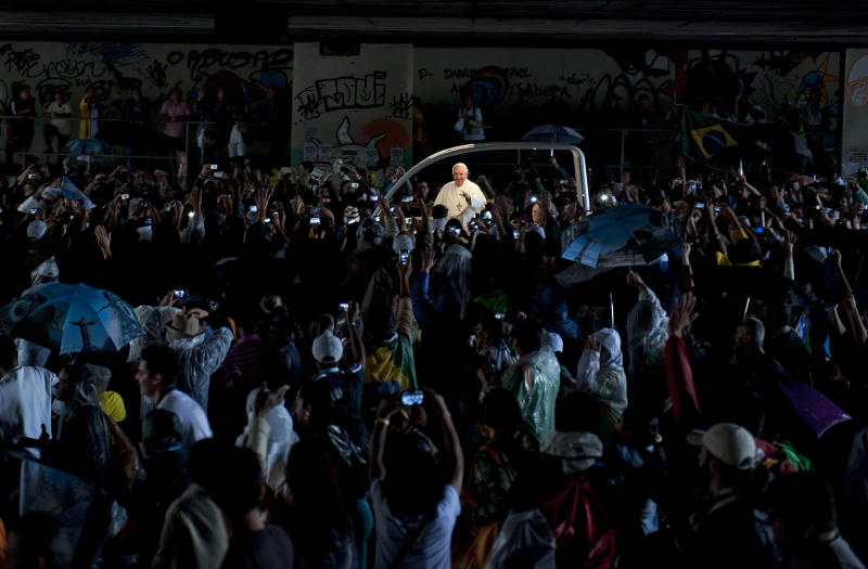 People greet Pope Francis as he travels through a road tunnel in his popemobile in Rio de Janeiro, Brazil, early Saturday, July 27, 2013. Pope Francis on Saturday challenged bishops from around the world to get out of their churches and preach, and to have the courage to go to the farthest margins of society to find the faithful. (AP Photo/Nicolas Tanner)