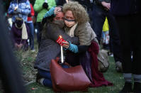 Mourners hug at a vigil for the victims of a mass shooting at a grocery store earlier in the week, Wednesday, March 24, 2021, outside the courthouse in Boulder, Colo. (AP Photo/David Zalubowski)