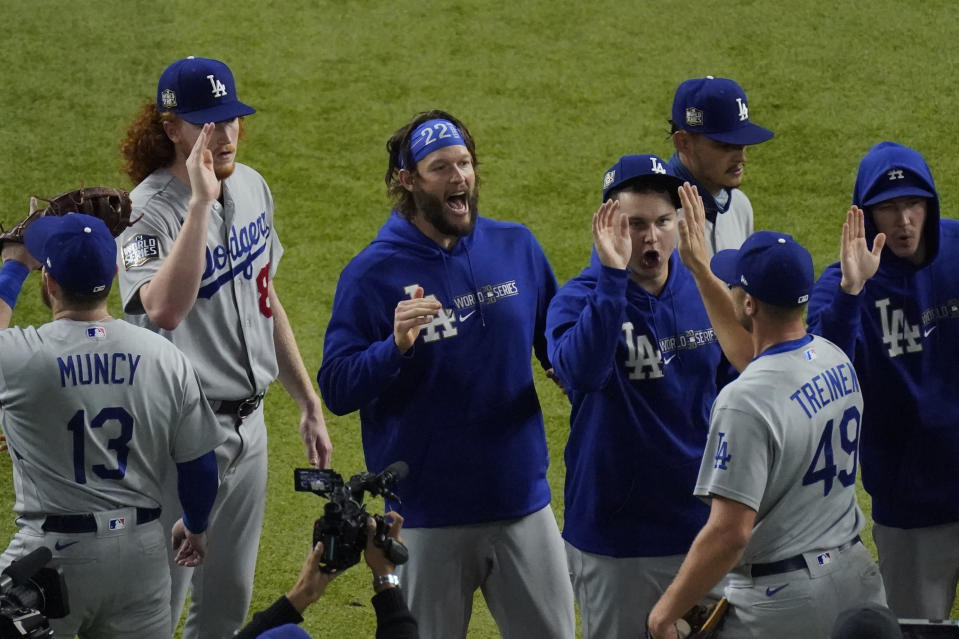 Los Angeles Dodgers starting pitcher Clayton Kershaw, center, celebrates after their win against the Tampa Bay Rays in Game 5 of the baseball World Series Sunday, Oct. 25, 2020, in Arlington, Texas. Dodgers beat the Rays 4-2 to lead the series 3-2 games. (AP Photo/Sue Ogrocki)