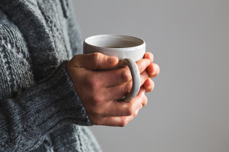 Female hands holding a mug of tea, coffee or hot chocolate.