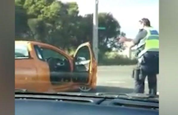 The police officer can be seen pointing his gun at the driver. Source: 7 News