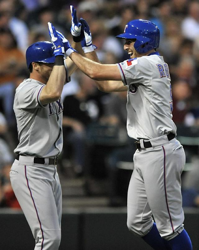 Texas Rangers' Adam Rosales right, celebrates at home plate with teammate Craig Gentry after hitting a two-run home run during the second inning of a baseball game against the Chicago White Sox in Chicago, Friday, Aug. 23, 2013. (AP Photo/ Paul Beaty)