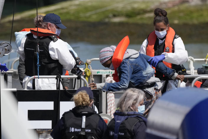 A woman and a child thought to be migrants are disembarked from a British border force vessel in Dover, south east England, Thursday, July 22, 2021. The number of undocumented migrants reaching Britain in small boats this year has surpassed the total for all of 2020, as people smugglers take advantage of good weather to cross the English Channel from France. (AP Photo/Matt Dunham)
