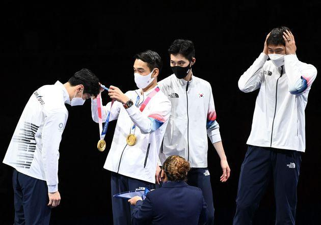 South Korea fencers receive their gold medals on the podium during the medal ceremony for the men's sabre team on July 28. (Photo: MOHD RASFAN via Getty Images)