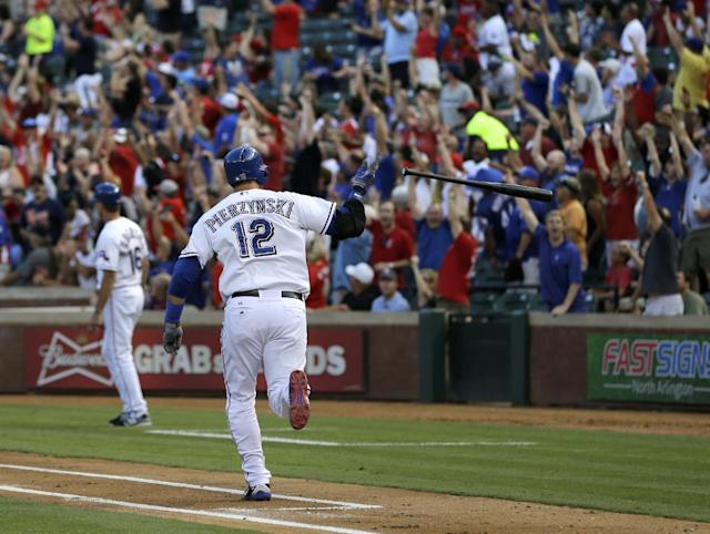 Fans stand and cheer as Texas Rangers' A.J. Pierzynski (12) flips the bat running down the first base line on his two-run home run off of Oakland Athletics starting pitcher Dan Straily in the second inning of a baseball game, Monday, June 17, 2013, in Arlington, Texas. (AP Photo/Tony Gutierrez)
