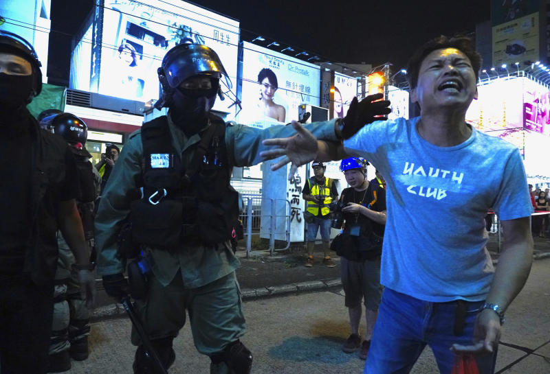 A local resident argues with a police officer in Hong Kong on Saturday, Oct. 26, 2019. Hong Kong authorities have won a temporary court order banning anyone from posting personal details or photos of police officers online, in their latest effort to clamp down on the city's protest movement. (AP Photo/Vincent Yu)