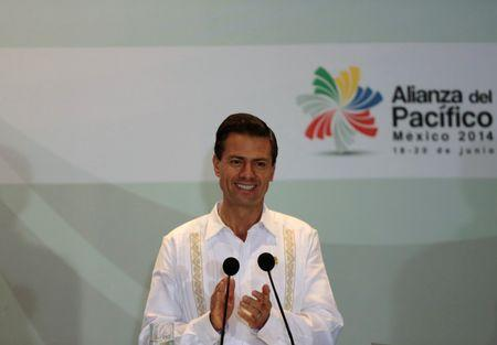 Mexico's President Enrique Pena Nieto applauds after the signing of agreements at the second day of the 2014 Alianza del Pacifico political summit in Punta Mita