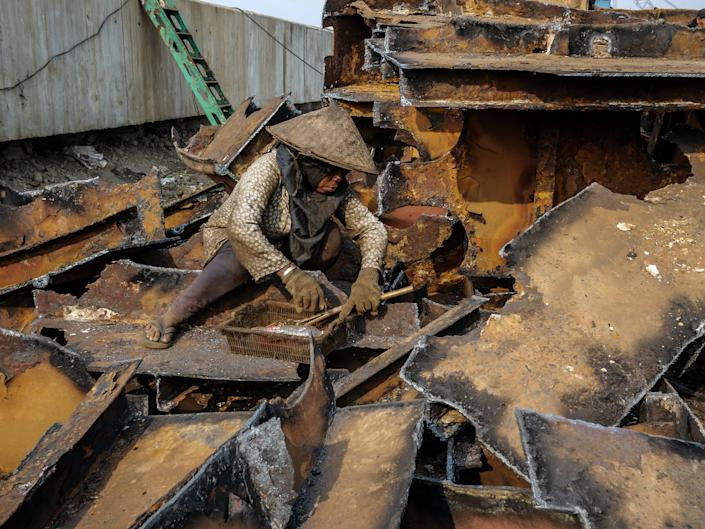 A worker gains a metal from a demolished old ships at a shipbreaking yards Kalibaru in Jakarta, Indonesia on September 27, 2018.