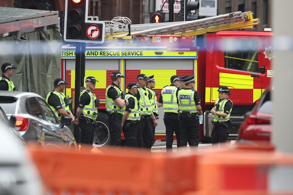 Police officers stand by a screen which has been erected at the scene in West George Street, Glasgow, where a man has been shot by an armed officer after another officer was injured during an attack.