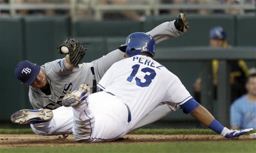 CORRECTS CONRAD TO THIRD BASEMAN, INSTEAD OF SECOND BASEMAN - Kansas City Royals' Salvador Perez (13) slides and is tagged out by Tampa Bay Rays third baseman Brooks Conrad while trying to get back to first base after being caught in a rundown during the third inning of a baseball game Monday, June 25, 2012, in Kansas City, Mo. (AP Photo/Jeff Roberson)