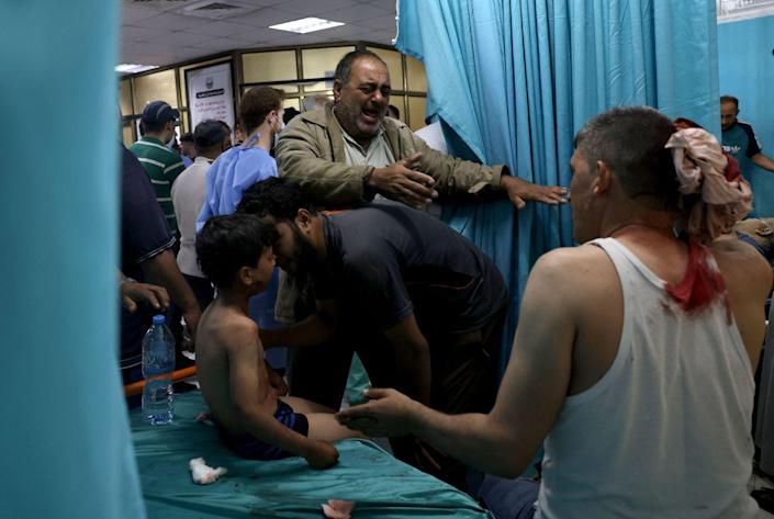 Wounded Palestinians sit at a hospital in Gaza.