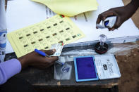 Election officials check identification papers of people who lined up to vote in Burkina Faso's presidential and legislative elections as polling stations open in Ouagadougou, Sunday, Nov. 22, 2020. (AP Photo/Sophie Garcia)