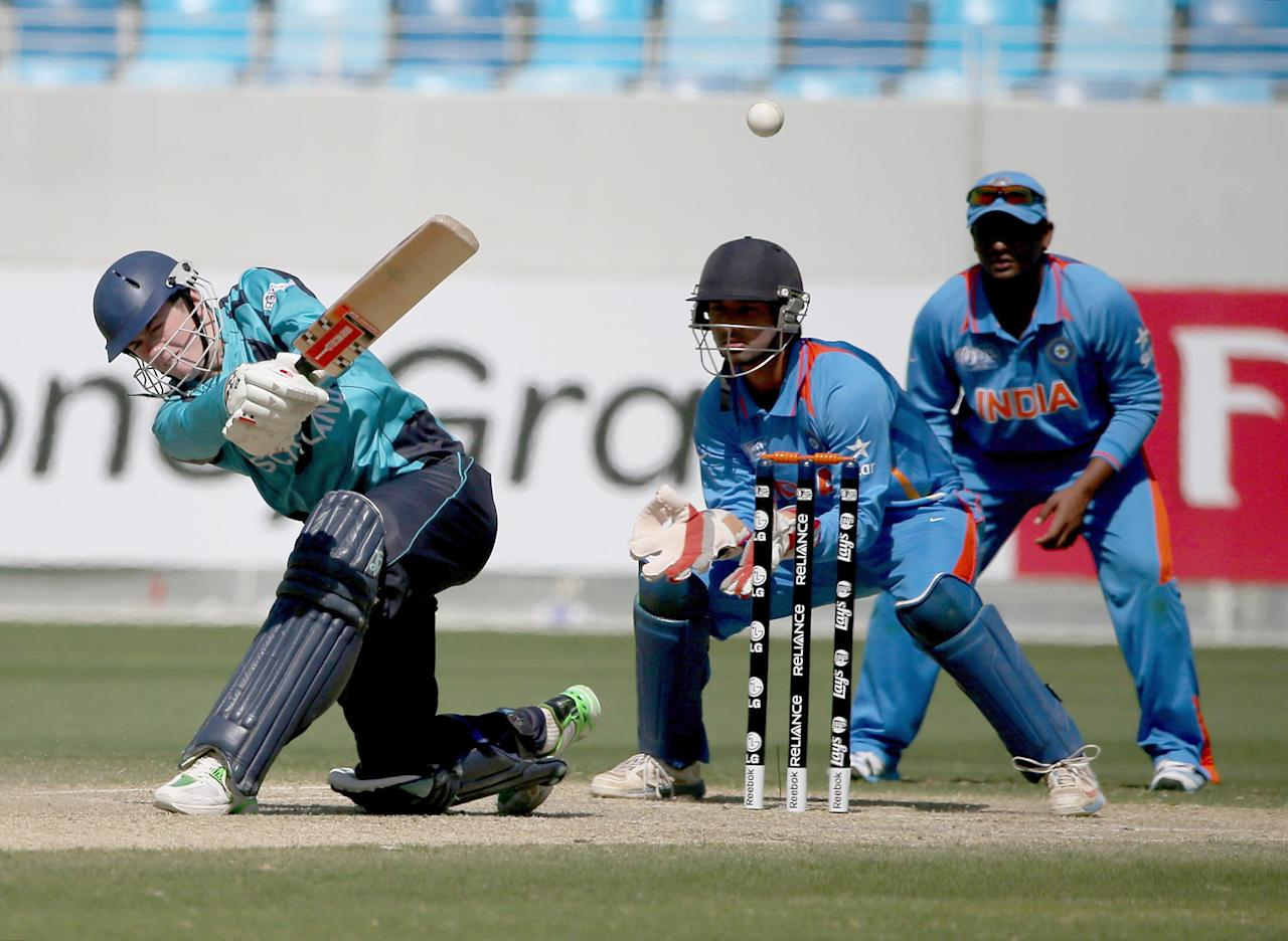 DUBAI, UNITED ARAB EMIRATES - FEBRUARY 17:  Gavin Main of Scotland bats as Ankush Bains of India looks on during the ICC U19 Cricket World Cup 2014 match between India and Scotland at the Dubai Sports City Cricket Stadium on February 17, 2014 in Dubai, United Arab Emirates.  (Photo by Francois Nel - IDI/IDI via Getty Images)