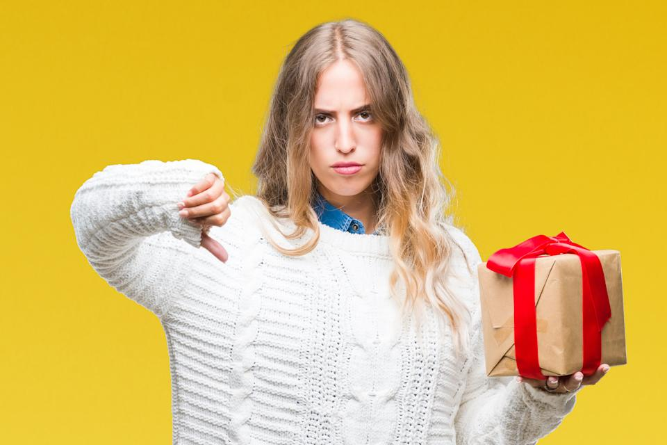 Young blonde woman holding gift over isolated background with angry face, negative sign showing dislike with thumbs down, rejection concept