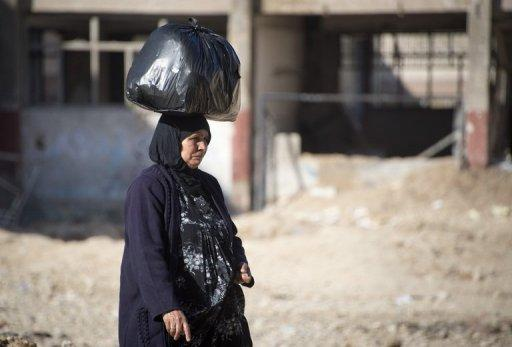 A woman carries foodstuffs on her head in the Aleppo neighbourood of Tariq al-Bab on December 8, 2012
