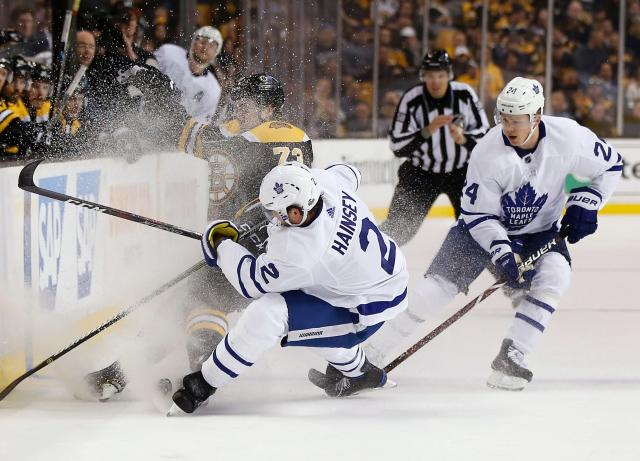 Boston Bruins' Charlie McAvoy (73) and Toronto Maple Leafs' Ron Hainsey (2) battle for the puck during the second period of Game 5 of an NHL hockey first-round playoff series in Boston, Saturday, April 21, 2018. (AP Photo/Michael Dwyer)