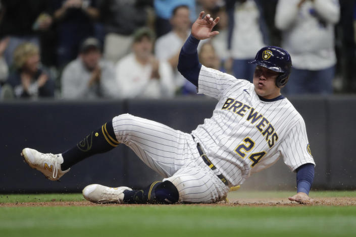 Milwaukee Brewers' Avisail Garcia (24) slides in safely at home to score on a single hit by Eduardo Escobar during the third inning of a baseball game against the New York Mets Saturday, Sept. 25, 2021, in Milwaukee. (AP Photo/Aaron Gash)