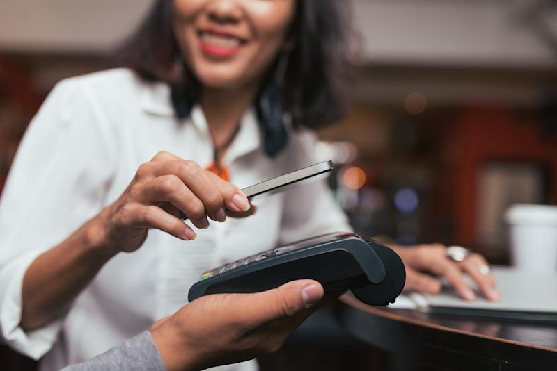 A woman using a contactless payment system on her phone