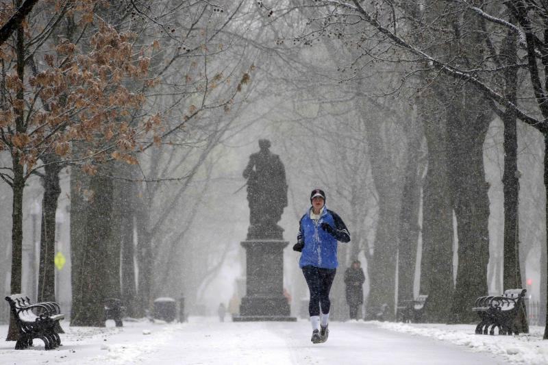 A runner runs in the snow in the park along Commonwealth Ave in Boston, Friday, Feb. 8, 2013. Snow began falling across the Northeast on Friday, ushering in what was predicted to be a huge, possibly historic blizzard and sending residents scurrying to stock up on food and gas up their cars. The storm could dump 1 to 3 feet of snow from New York City to Boston and beyond. (AP Photo/Gene J. Puskar)