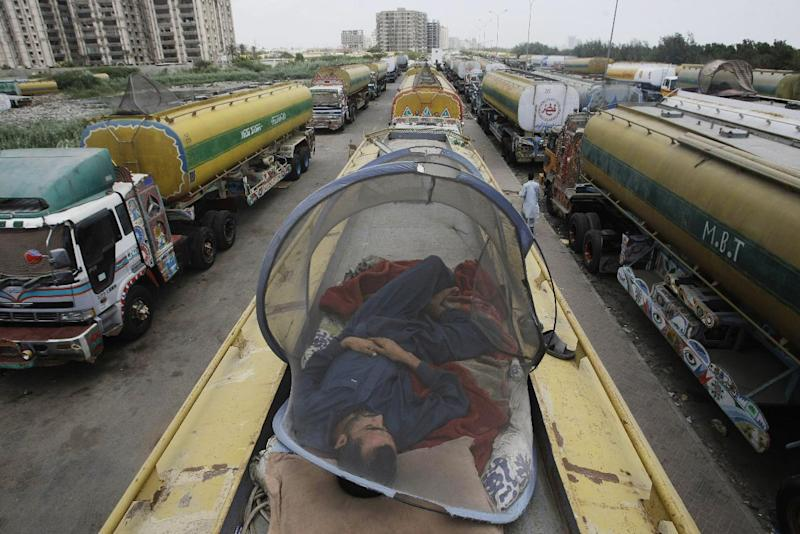 A man takes nap on one of oil tankers used to transport NATO fuel supplies to neighboring Afghanistan, in Karachi, Pakistan, Thursday, May 17, 2012. Pakistan's president announced Thursday that he will attend the upcoming NATO summit in Chicago, accepting an invitation that was given after the country indicated it plans to end its six-month blockade of supplies meant for coalition troops in Afghanistan. (AP Photo/Fareed Khan)
