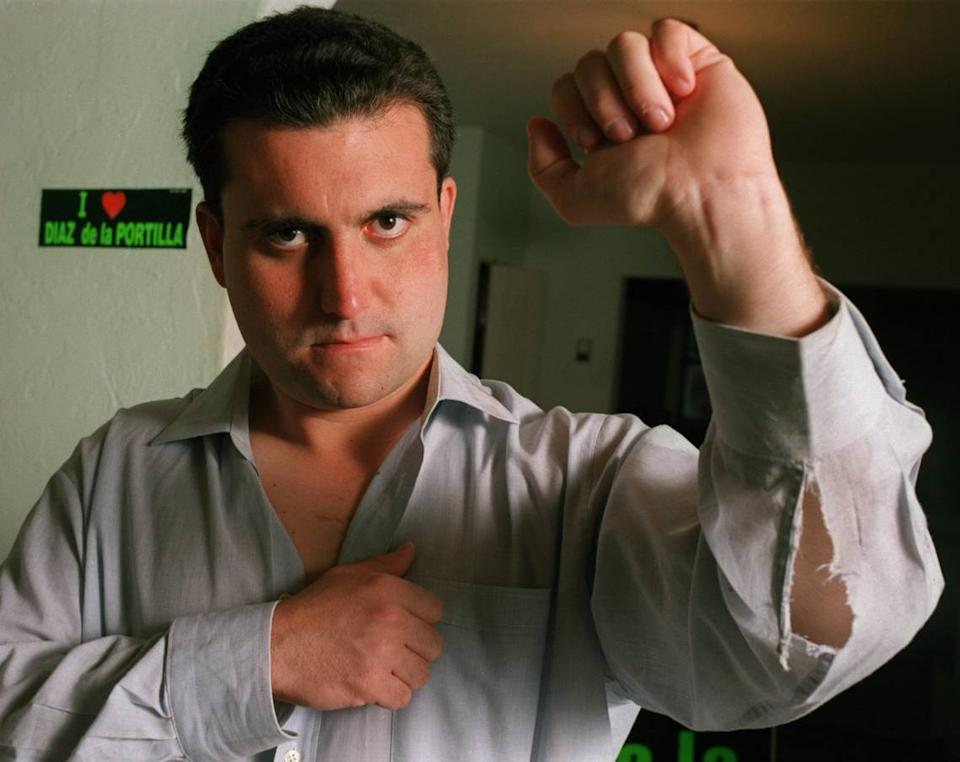 Renier Diaz de la Portilla, state legislator, shows off his ripped shirt and bruises he suffered during a fight at Radio Mambi in September 2000.