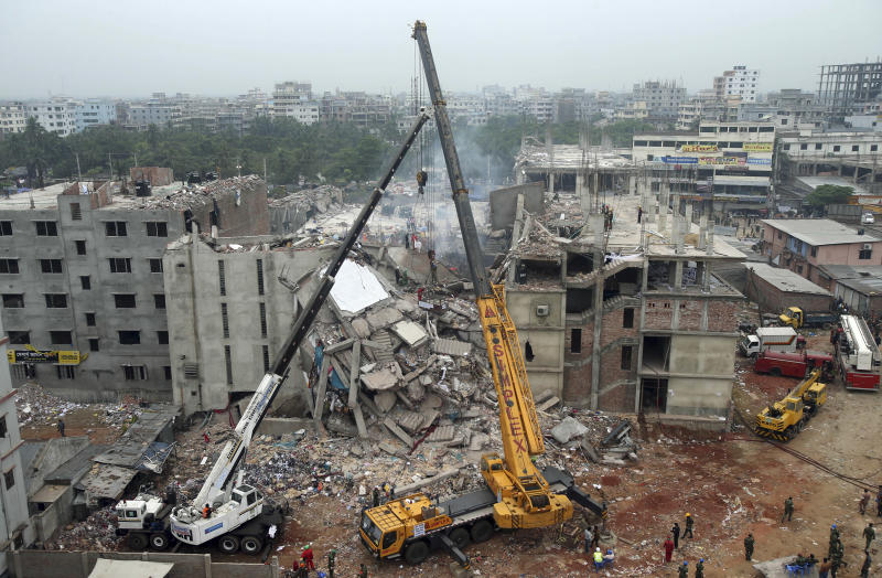 FILE - n this April 29, 2013 file photo, a collapsed garment factory building is seen from a building nearby as a crane prepares to lift the fallen ceiling in Savar, near Dhaka, Bangladesh. Bangladeshi garment factories are routinely built without consulting engineers. The collapse of the Rana Plaza building killed 1,129 people in the worst garment industry tragedy. Many are located in commercial or residential buildings not designed to withstand the stress of heavy manufacturing. Some add illegal extra floors atop support columns too weak to hold them, according to a survey of scores of factories by an engineering university. The textiles minister said a third inspection, conducted by the government, could show that as many as 300 factories were unsafe. (AP Photo/Wong Maye-E, File)