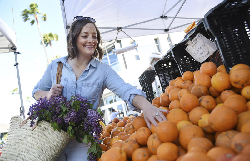 "This April 10, 2019 photo shows Gaby Dalkin shopping for oranges at Santa Monica Downtown Farmers Market in Santa Monica, Calif. Dalkin, the chef behind the popular Website and social media accounts, ""What's Gaby Cooking,"" is forging her own path. Every Monday she posts a live demo to Instagram as she cooks dinner which has become appointment viewing for some fans. Her husband films it and reads questions from viewers as she's cooking. (AP Photo/Chris Pizzello)"
